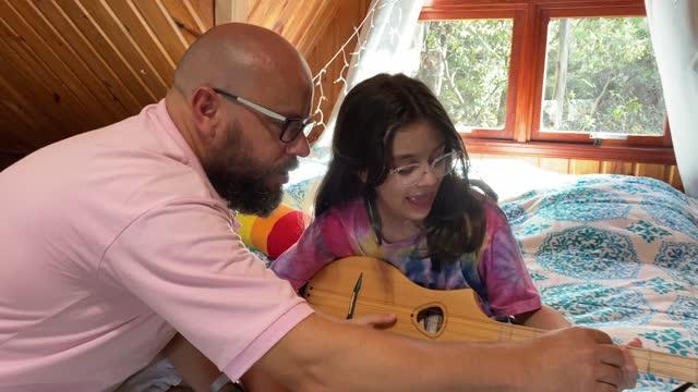 vídeos de stock, filmes e b-roll de filha aprendendo a tocar violão com o pai - ukulele