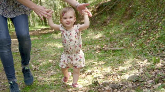 tochter lernt mit mutter im wald laufen - weibliches baby stock-videos und b-roll-filmmaterial