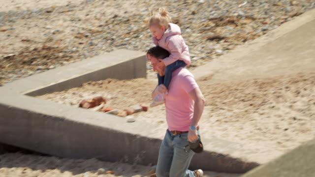 Dotter på far axlar på stranden