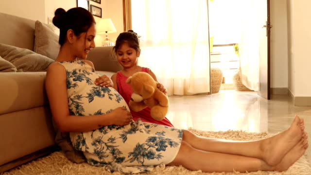ms daughter playing with pregnant mother while sitting on rug in living room / india - pregnant stock videos & royalty-free footage