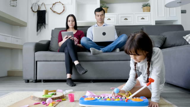 daughter playing with toys on floor while father and mother working in background - famiglia con figlio unico video stock e b–roll