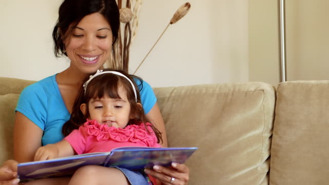 daughter pointing to pictures as mother reads to her - mexican ethnicity stock videos & royalty-free footage