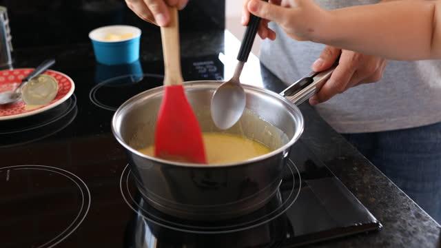 娘は彼女の父がかき混ぜながら鍋にチョコレートパウダーを注ぎます。 - dia点の映像素材/bロール