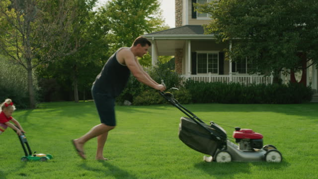 daughter pushing toy lawnmower following father mowing lawn / pleasant grove, utah, united states - prato rasato video stock e b–roll