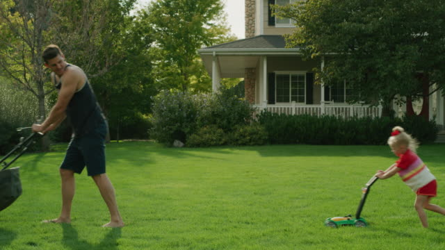 daughter pushing toy lawnmower following father mowing lawn / pleasant grove, utah, united states - full length点の映像素材/bロール