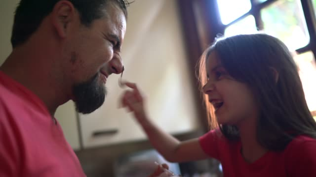 daughter putting melted chocolate on father's face at home - enjoyment stock videos & royalty-free footage