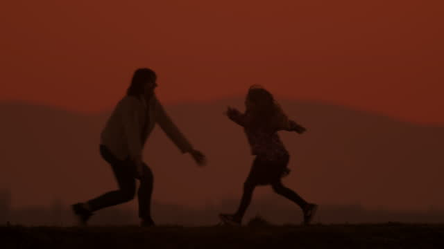 slo mo ls daughter running into mother's arms on a hill at dusk - elementary age stock videos & royalty-free footage