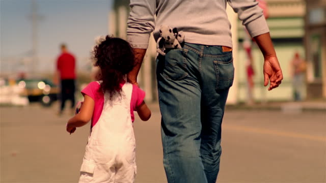vídeos de stock, filmes e b-roll de daughter running to grab father's hand as they walk up street / girl waving american flag / california - cultura americana