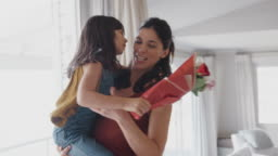 Daughter Running To Mother And Handing Her Bunch Of Flowers To Celebrate Birthday Or Mothers Day
