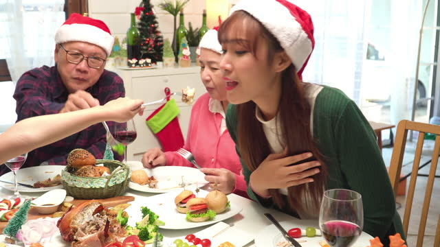 daughter sharing bread, christmas eve food with mother, southeast asian multi-generation family seating around food dinner for christmas celebration of december's holiday in a home decorated with christmas tree and ornament. - 65 69 years stock videos & royalty-free footage