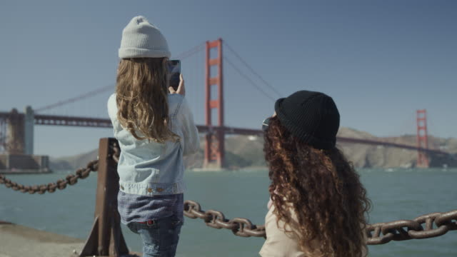 daughter showing mother cell phone photograph near golden gate bridge / san francisco, california, united states - golden gate bridge stock videos & royalty-free footage