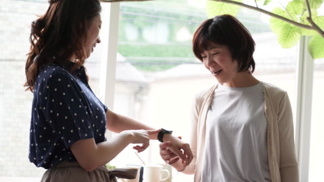 daughter showing smart watch for mother - japanese mom stock videos & royalty-free footage
