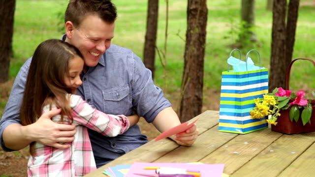 vidéos et rushes de fille montre père main fête des pères carte.   plein air.   enfant parent. - donner