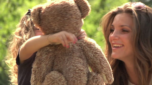 ms slo mo daughter smiles she receives teddy bear from mother  / new york, new york, united states   - spielzeug stock-videos und b-roll-filmmaterial