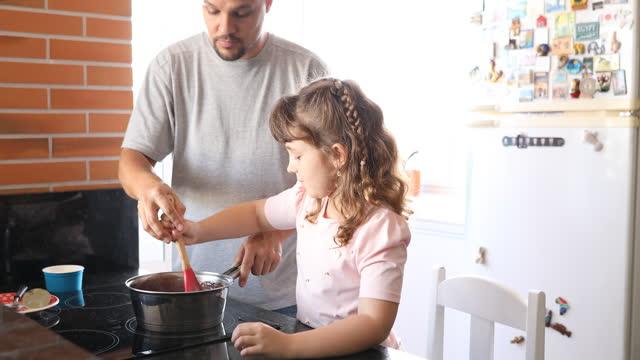 彼女の父親が彼女を導いている間、娘は鍋をかき混ぜる - dia点の映像素材/bロール