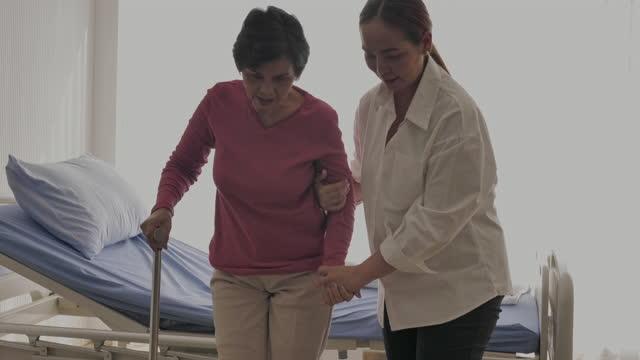 vídeos y material grabado en eventos de stock de hija apoyando a la madre caminar - edificio médico