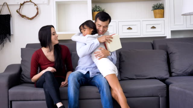 stockvideo's en b-roll-footage met dochter verrassende vader en moeder met cadeau thuis in de woonkamer, gelukkige familie concept - verjaardagskado