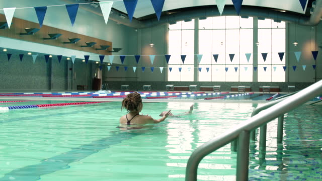 Daughter swimming towards her mother in a pool