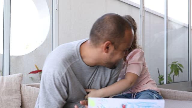 彼は父の日から彼女の引き分けを保持しながら、娘は彼女の父親をくすぐる - dia点の映像素材/bロール