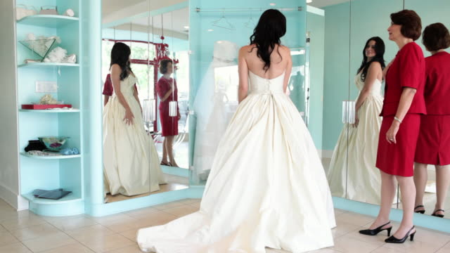 Daughter trying on wedding dress with mother