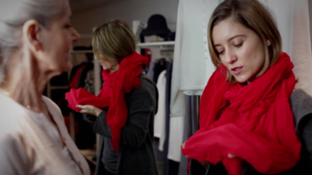 vidéos et rushes de cu pan daughter trying outfits in fitting room, mother assisting - habillement