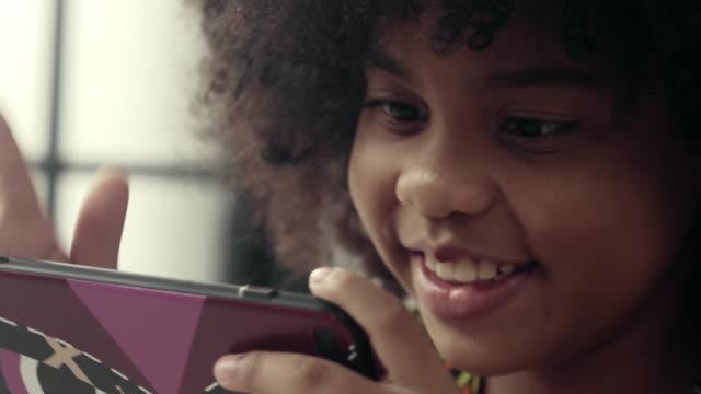 vídeos de stock, filmes e b-roll de filha que usa a tabuleta digital na home da sala de visitas - jogo de lazer