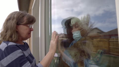a daughter visiting her quarantined mother preventing contracting corona virus through the window - social issues stock videos & royalty-free footage