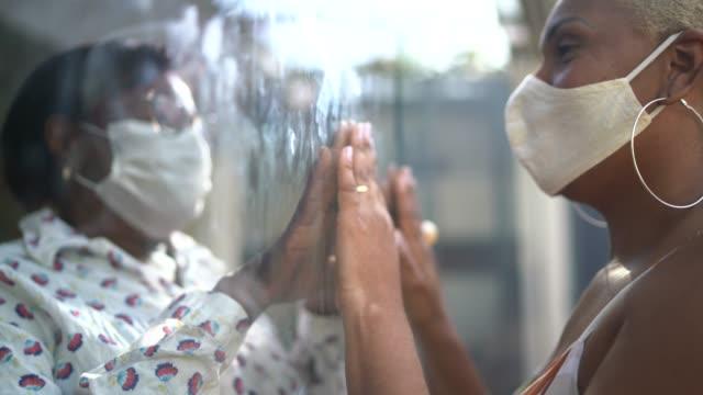 vídeos de stock, filmes e b-roll de filha visitando mãe em quarentena, comunicando-se através de uma janela de vidro - avó