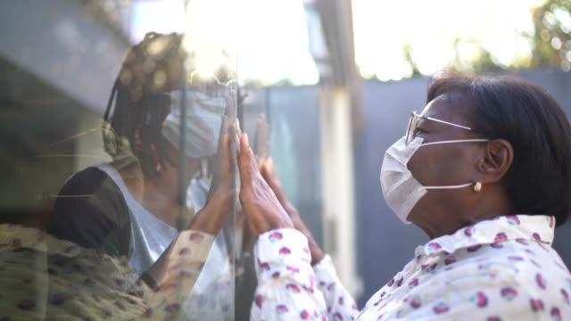 vídeos de stock, filmes e b-roll de filha visitando mãe em quarentena, comunicando-se através de uma janela de vidro - vínculo