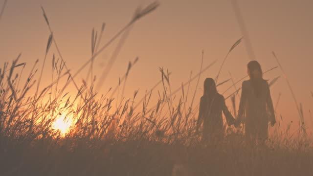 Tochter mit ihrer Mutter bei Sonnenuntergang wandern