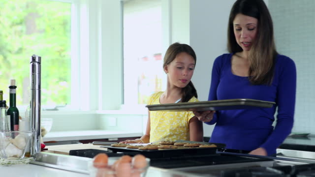 ms ds daughter watching mom put tray of cookies in oven in kitchen of contemporary home - stove stock videos & royalty-free footage