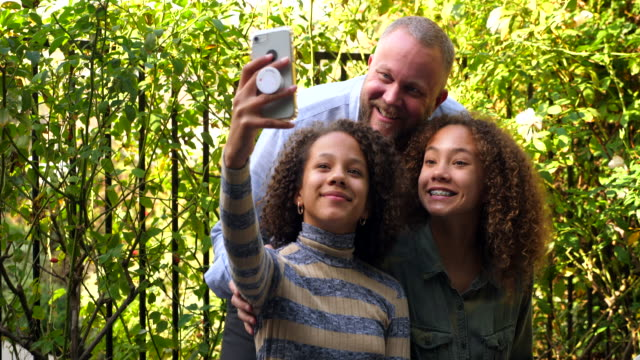 ms daughters taking selfie with father during backyard family picnic - single father stock videos & royalty-free footage