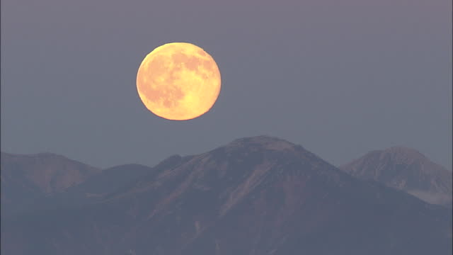 a daunting full moon hangs over the northern alps. - full moon stock videos & royalty-free footage