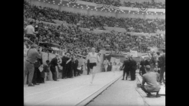 CU Dave Patrick of Villanova as he takes the lead in the indoor track race at the NCAA Track Championships in Detroit / crowd applaud as he wins the...