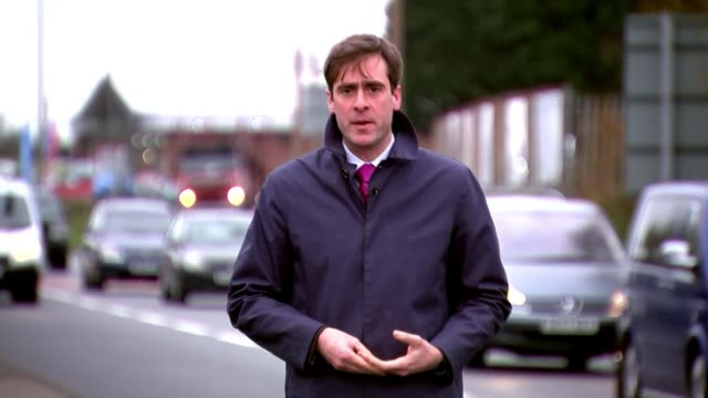 clayton williams trial reporter to camera purple and white flowers tilt up memorial photo 'wallasey docks link road north' road sign and makeshift... - 仮設追悼施設点の映像素材/bロール