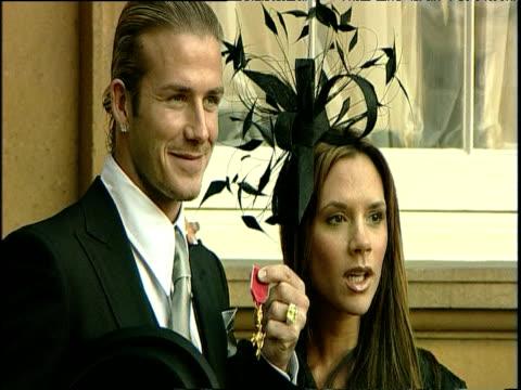 David and Victoria Beckham pose for photographers outside Buckingham Palace with David Beckham's OBE 27 Nov 03