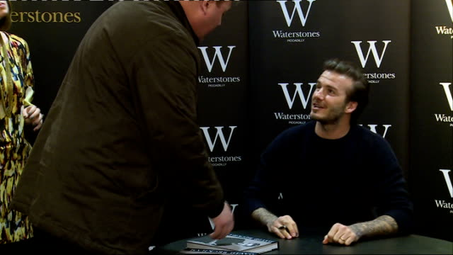 fans and david beckham photocall more beckham signing books and posing with fans for photographs / close shot signed copies of david beckham book... - biographie stock-videos und b-roll-filmmaterial