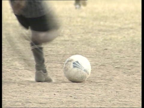 vidéos et rushes de david beckham meets nelson mandela; itn ext i/c soweto: ball kicked by south african boy gv south african boys playing football on dusty pitch boys... - donner un coup de pied