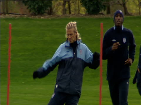 David Beckham practicing kicking exercises during England football training session other players in background London 15 Oct 03