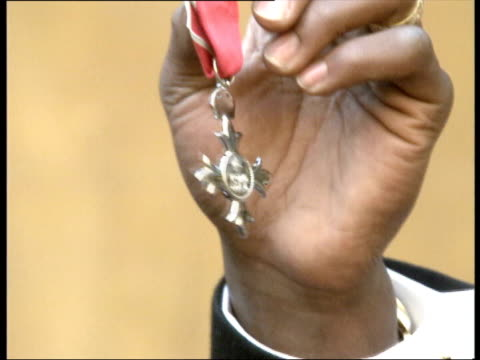 david beckham receives obe lib medal held by black hand - order of the british empire stock videos and b-roll footage