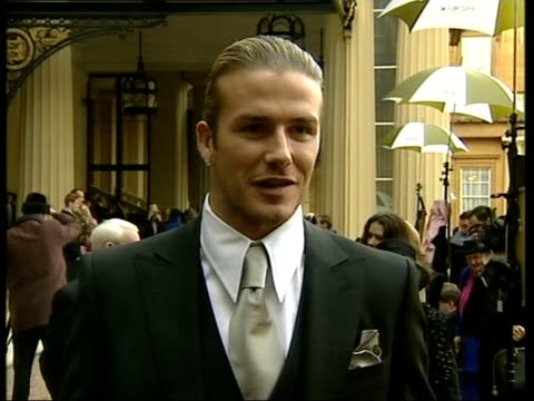 david beckham receives obe; pool ext david and victoria beckham posing for photocall with his grandparents joseph and peggy west cms ditto pull out... - autographing stock videos & royalty-free footage