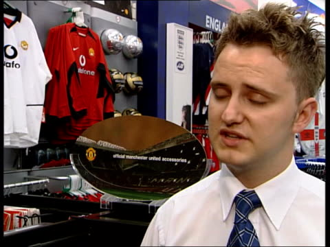 stockvideo's en b-roll-footage met david beckham transfer to real madrid itn manchester old trafford manchester united shop worker removing photograph of david beckham from wall pan... - getal 7