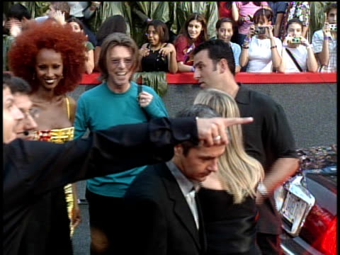David Bowie and Iman arriving on the red carpet at the 1999 MTV Video Music Awards and waving to the camera