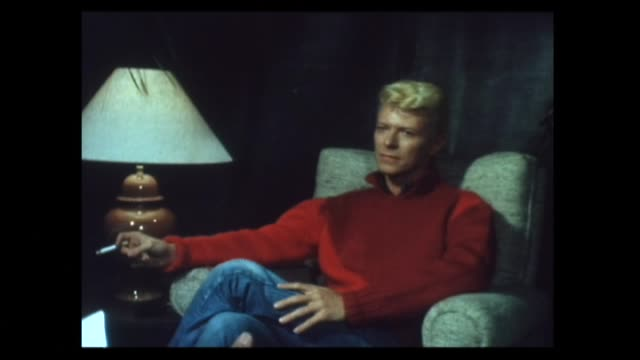 David Bowie smoking cigarette in 1983 during interview about enjoying current world tour which is the longest he has done