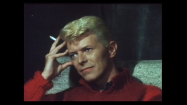 stockvideo's en b-roll-footage met david bowie smoking cigarette in 1983 during interview about sociological messages in music videos for the let's dance album - david bowie