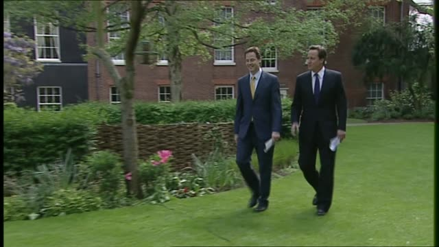 david cameron and nick clegg rose garden press conference itn pool london downing street ext nick clegg along downing street greeted by david cameron... - ニック クレッグ点の映像素材/bロール