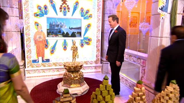 david cameron celebrates diwali on visit to hindu temple in london ***flash gvs interior of temple / david and samantha cameron along and perform... - hinduism stock videos & royalty-free footage