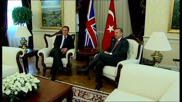 David Cameron handshake with Turkish Prime Minister Recep Tayyip Erdogan INT Cameron and Erdogan seated in armchairs for photocall then standing for...