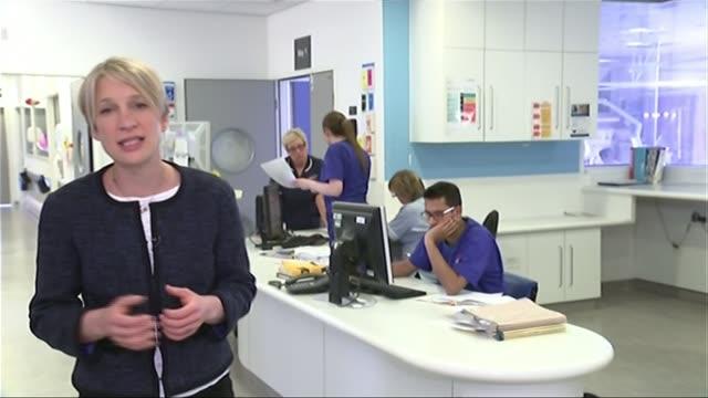 david cameron outlines plans for seven days a week nhs medical staff at desks and along pan reporter to camera nurse walking along corridor - itvイブニングニュース点の映像素材/bロール