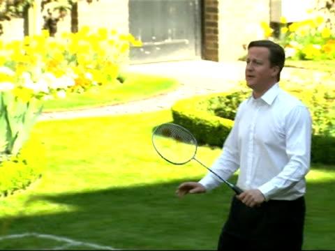 vídeos de stock, filmes e b-roll de david cameron plays badminton with schoolchildren at event to promote london olympics - david cameron político